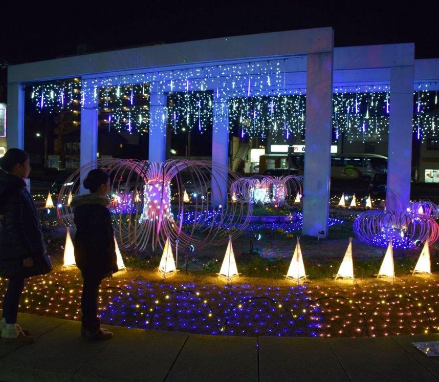 青と白の「光のシャワー」や竹で作られた「願いの花」などの明かりがJR丸亀駅前を彩っている=丸亀市浜町
