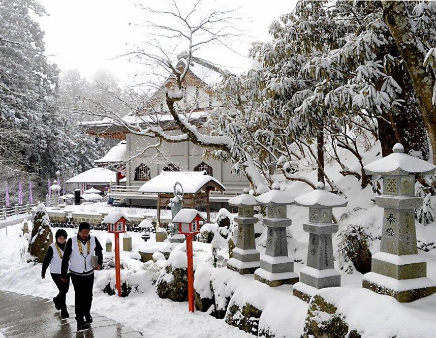 雪景色の雲辺寺境内を歩くお遍路さん(資料)