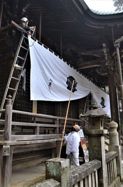本堂に新しいまん幕を張る歓喜会のメンバー=香川県高松市牟礼町、八栗寺