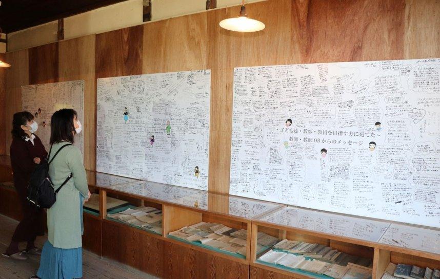 全国から訪れた教師らが記したメッセージに見入る観光客=香川県小豆郡小豆島町田浦、岬の分教場