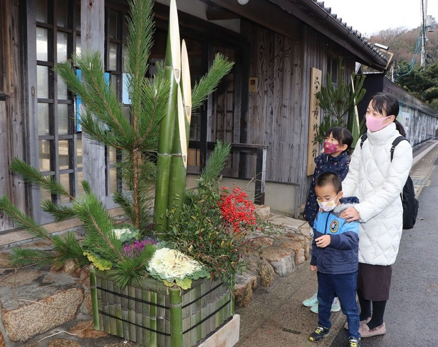 新春の華やかさを感じさせる門松に見入る観光客=香川県小豆島町田浦、二十四の瞳映画村